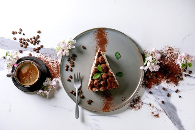 Plakje zelfgemaakte glutenvrije tiramisu traditioneel italiaans dessert bestrooid met cacaopoeder, bloeiende appelboom, koffie, muntblaadjes, koffiebonen over wit marmeren oppervlak. bovenaanzicht, plat gelegd