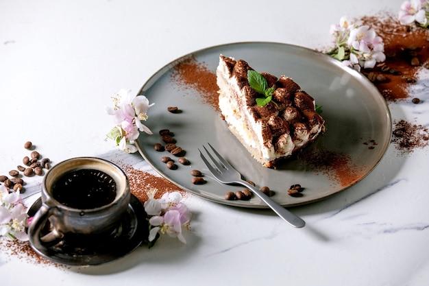 Plakje zelfgemaakte glutenvrije tiramisu traditioneel italiaans dessert bestrooid met cacaopoeder versierd met bloeiende appelboom, koffie, muntblaadjes en koffiebonen over wit marmeren oppervlak.