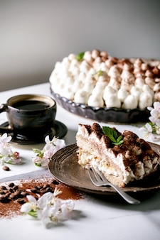 Plakje zelfgemaakte glutenvrije tiramisu traditioneel italiaans dessert bestrooid met cacaopoeder versierd met bloeiende appelboom, koffie, muntblaadjes, koffiebonen over witte marmeren tafel. detailopname