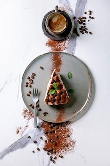 Plakje zelfgemaakte glutenvrije tiramisu traditioneel italiaans dessert bestrooid met cacaopoeder versierd met koffie, muntblaadjes en koffiebonen over wit marmeren oppervlak. bovenaanzicht, plat gelegd