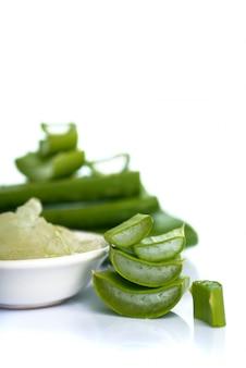 Plakjes aloë vera blad en aloë vera gel in een kom op een witte ondergrond. aloë vera is een zeer nuttig kruidengeneesmiddel voor huidverzorging en haarverzorging.