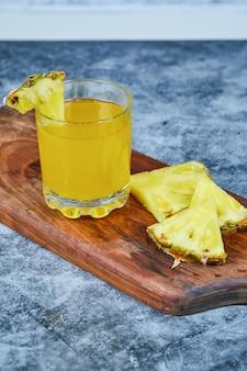 Plakjes ananas en ananassap op een houten bord.
