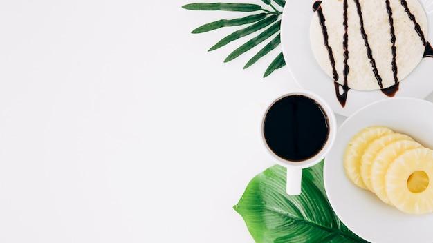 Plakjes ananas; tortilla's en koffie drinken op groene bladeren tegen een witte achtergrond