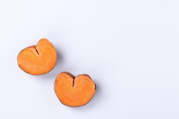 Plakjes biologische wortelen in de vorm van harten, concept voor valentijnsdag, liefdeswortelen, kopieerruimte, bovenaanzicht