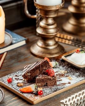 Plakjes brownie met walnoot gegarneerd met chocoladesiroop en suikerpoeder