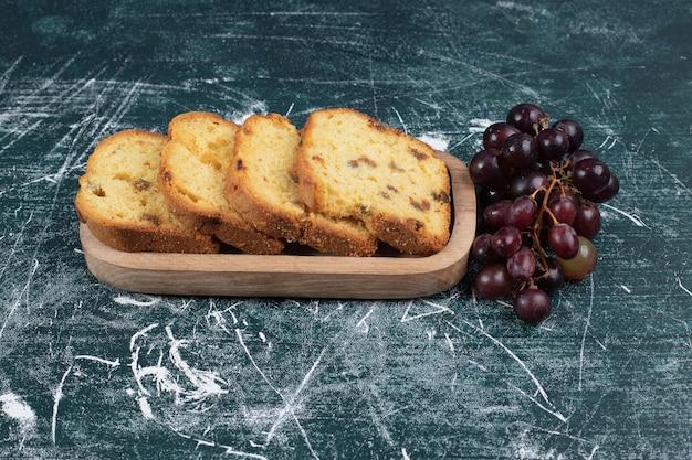 Plakjes cake met rozijnen en druiven op marmeren muur.