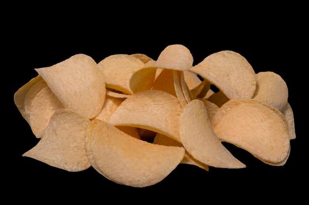 Plakjes chips close-up op een zwarte achtergrond