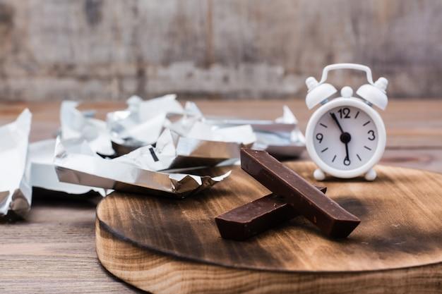 Plakjes chocolade, een stapel lege wikkels en een wekker op een houten tafel. concept van het eten van zoete tijd en voeding.