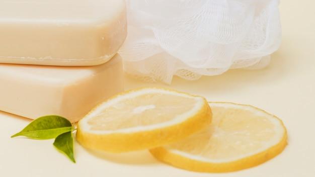 Plakjes citroen; zeep en luffa op gekleurde achtergrond
