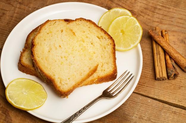 Plakjes citroentaart op een witte plaat en op een houten tafel in een bovenaanzicht