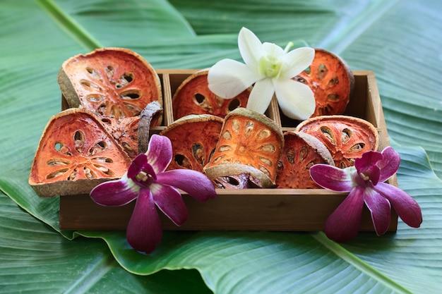 Plakjes droog bael-fruit in houten kist.