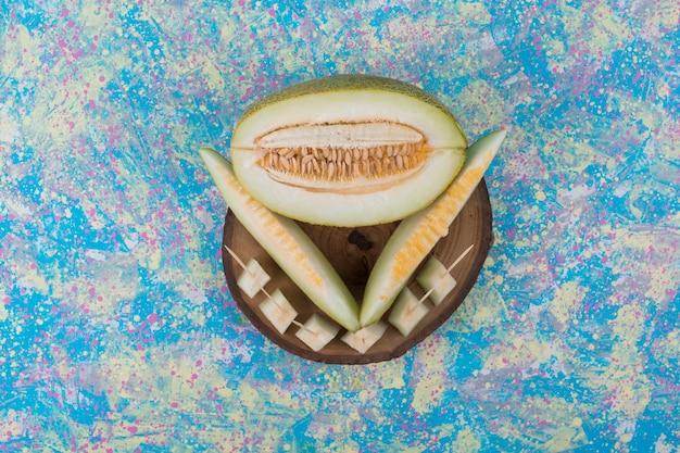 Plakjes en blokjes meloen op een houten schaal in het midden.