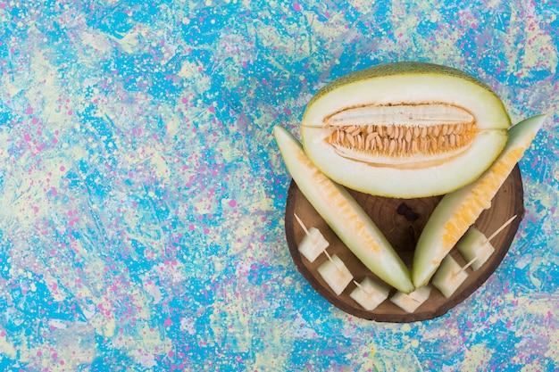 Plakjes en blokjes meloen op een houten schotel, bovenaanzicht
