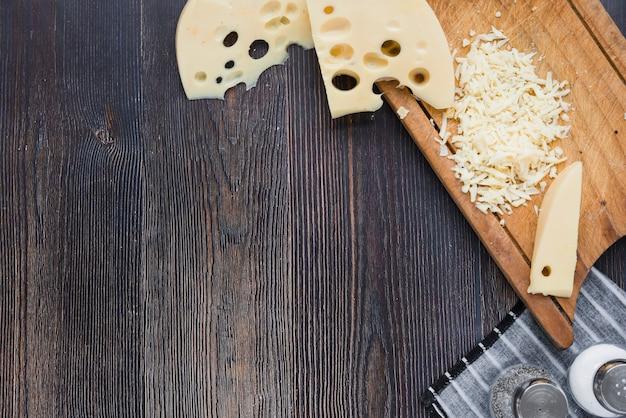 Plakjes en geraspte maasdam-kaas op een houten bord boven het zwarte bureau
