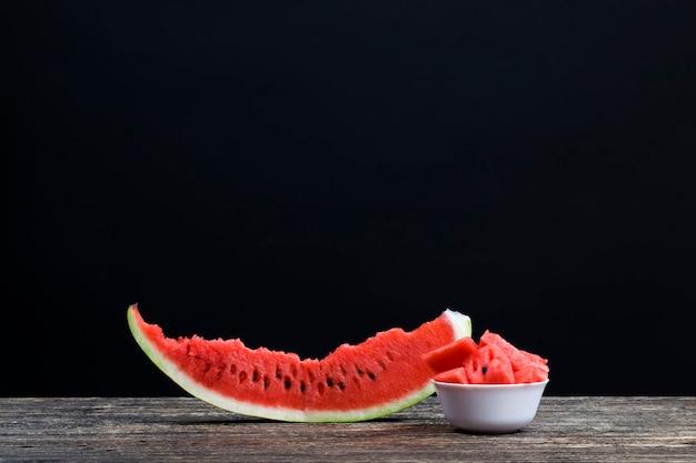 Plakjes en stukjes rode sappige watermeloen gesneden op de tafel, natuurlijk voedingsproduct