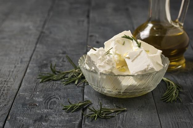 Plakjes fetakaas met olijfolie en kruiden op een houten tafel. natuurlijke kaas gemaakt van schapenmelk.
