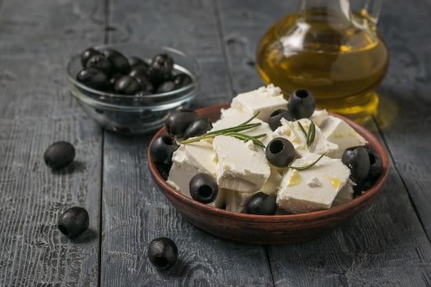 Plakjes fetakaas, zwarte olijven en olijfolie op een houten tafel. natuurlijke kaas gemaakt van schapenmelk.