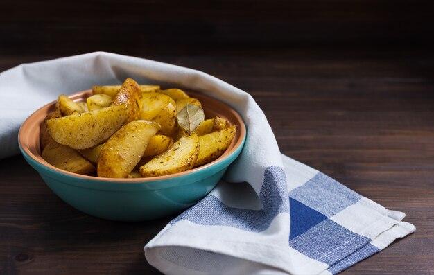 Plakjes gebakken aardappelen met kruiden in een plaat