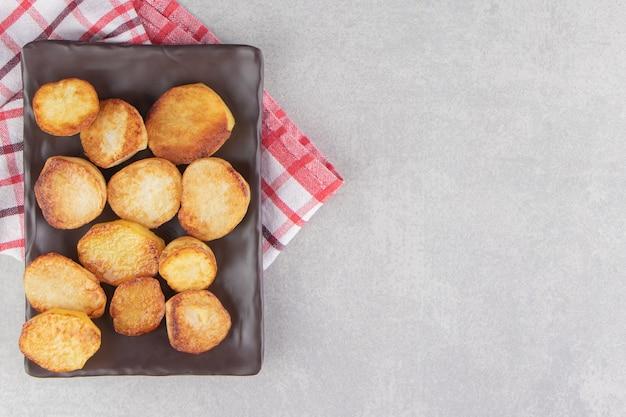 Plakjes gebakken aardappelen op bruine plaat.