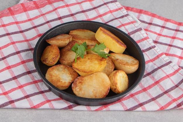 Plakjes gebakken aardappelen op zwarte plaat.