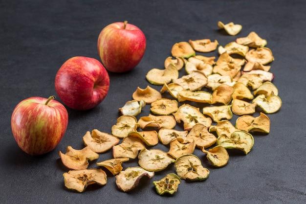 Plakjes gedroogde appels en verse rode appels. veganistisch tussendoortje. kopieer ruimte