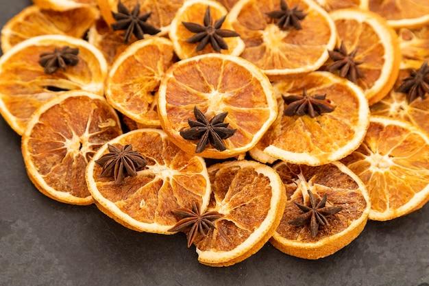 Plakjes gedroogde sinaasappel en steranijs op zwarte steen. selectieve aandacht.
