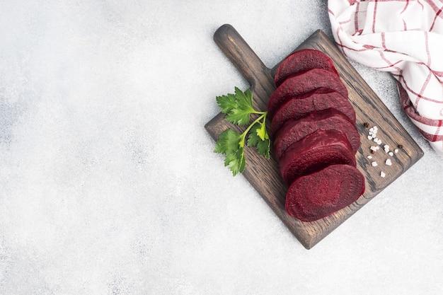 Plakjes gekookte rode biet op een snijplank met peterselie bladeren op een rustieke houten tafel. kopieer ruimte,
