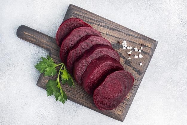 Plakjes gekookte rode biet op een snijplank met peterselieblaadjes op een houten rustieke achtergrond. kopieer ruimte,