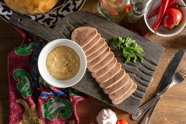 Plakjes gekookte rundertong met mierikswortel en koriander, in plakjes gesneden en geserveerd op een houten snijplank