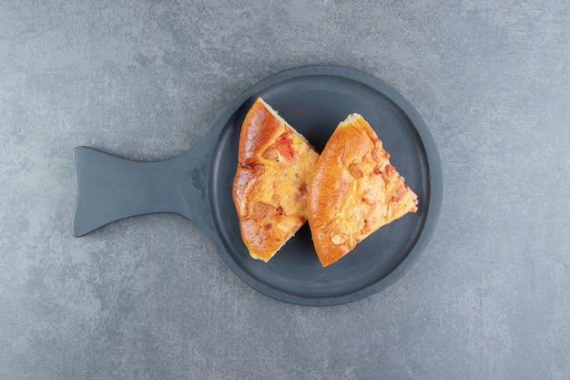 Plakjes gemengde pizza op zwarte snijplank.