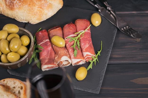 Plakjes gerookte ham of spaanse jamon serrano of italiaanse prosciutto crudo met glas rode wijn