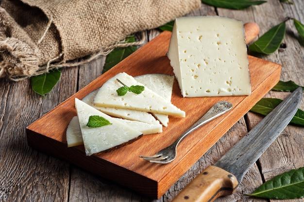 Plakjes gezouten manchego-kaas op een houten bord met een rustieke achtergrond