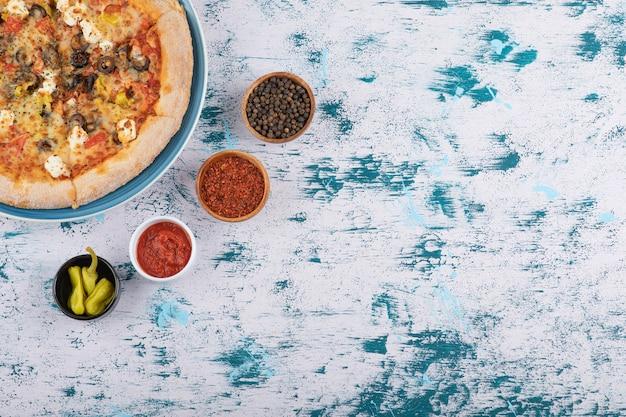 Plakjes hete pizza met peperkorrels en peperpoeder op een marmeren achtergrond.