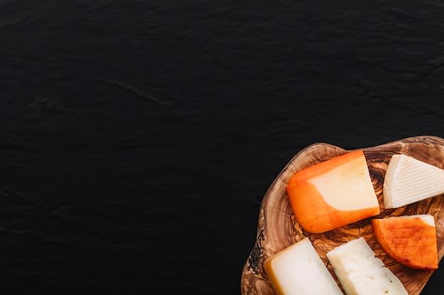 Plakjes kaas op een stuk hout