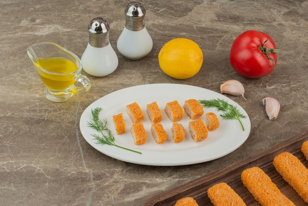Plakjes kipnuggets met tomaat, citroen, zout en peper.