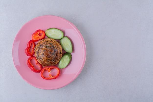 Plakjes komkommer en peper rond het koekje op plaat op marmeren tafel.