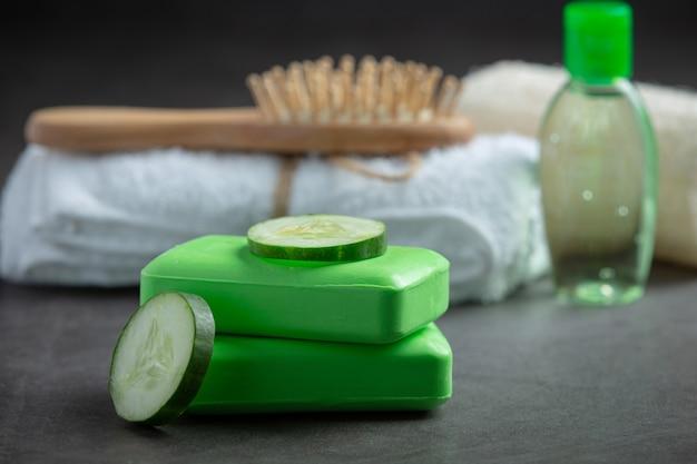 Plakjes komkommer en zeep op donkere achtergrond