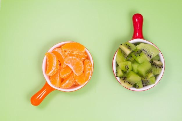 Plakjes mandarijn en kiwi plakjes in de tenen op een groene achtergrond