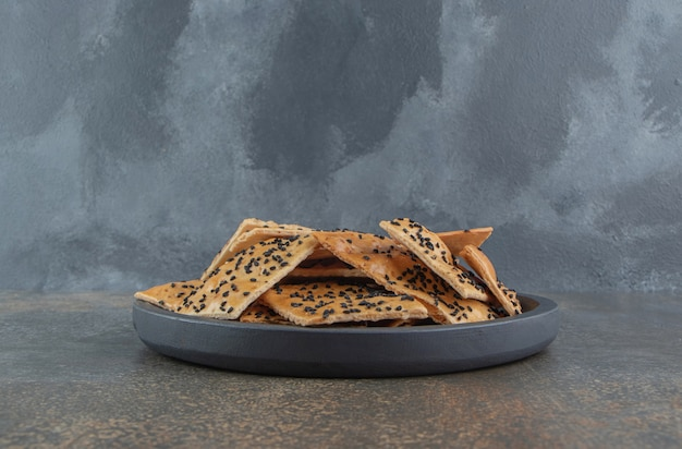 Plakjes met sesam bedekt brood opgestapeld in een kleine serveerschaal