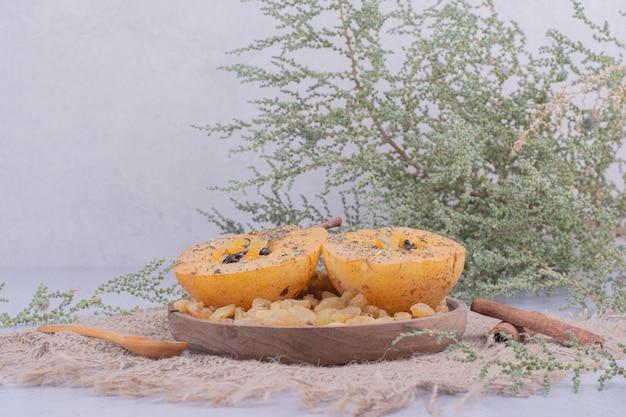 Plakjes peer in een houten plaat met rozijnen en kaneel