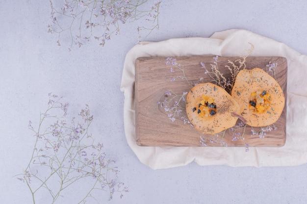 Plakjes peer met kruiden en specerijen op een houten bord