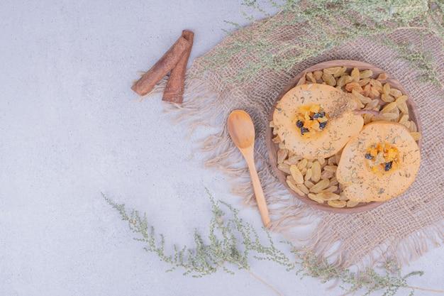 Plakjes peer met rozijnen en pijpjes kaneel in een houten plaat