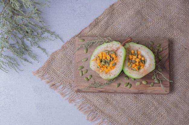 Plakjes peer met wortel, pompoenpitten en kruiden