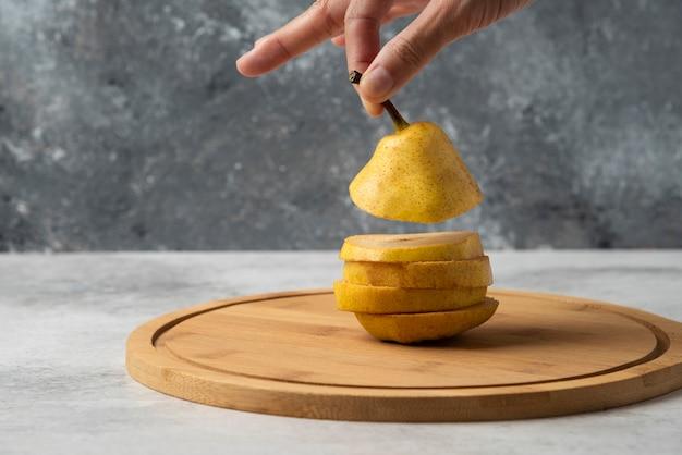 Plakjes peer op een houten schaal, er een oppakken.