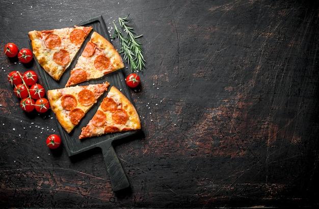 Plakjes pepperoni pizza met tomaten en rozemarijn op donkere rustieke tafel.