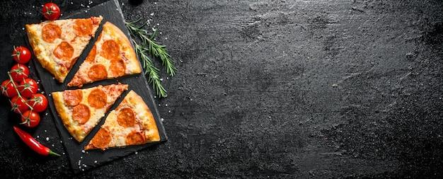 Plakjes pepperonispizza met tomaten en rozemarijn. op zwarte rustiek