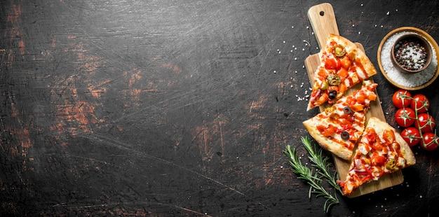 Plakjes pizza met kruiden, tomaten en rozemarijn op donkere rustieke tafel
