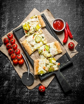 Plakjes plantaardige pizza met kerstomaatjes en saus in kom op zwarte rustieke tafel