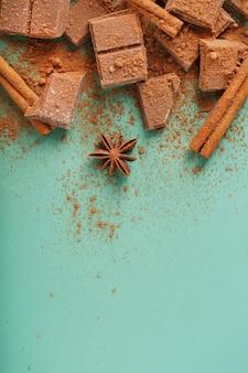 Plakjes pure chocolade met kaneel en kruiden op een pastelgroene ondergrond