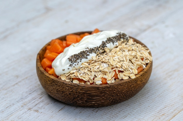 Plakjes rijp zoet papajafruit met havervlokken, chiazaadjes en witte yoghurt op kokosnootkom